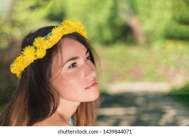 Portrait of a girl with a wreath of dandelions on his head, thoughtfully sitting in nature in the Park