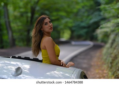 portrait of girl with yellow dress on the sunroof in the forest