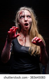 Portrait girl zombie on dark background with open mouth and bloody hands/Close-up portrait of zombie girl in studio.Horror.