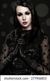 Portrait of girl-alien with black eyes in dark clothes