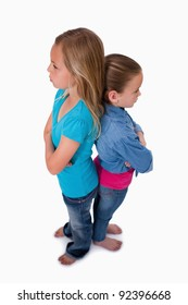 Portrait of girls standing back to back against a white background