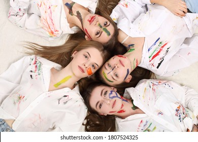 Portrait of girls in white color painted decorative, lies on the floor in the studio. Creative expressive abstract body painting art, copy space