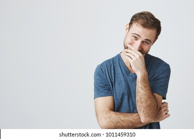 Portrait of glad attractive man with trendy hairdo and beard in blue t-shirt laughs happily at funny story or joke, being in good mood, expresses positive emotions, hides his smile behind his hand.