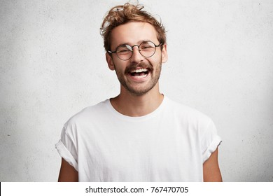 Portrait of glad attractive man with trendy hairdo, beard and mustache, laughs happily at funny story or joke, being in good mood, expresses positive emotions. Satisfied male student finishes work