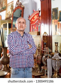 Portrait of glad cheerful positive  successful owner of antiques shop among vintage things