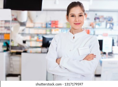 Portrait of glad cheerful positive woman pharmacist who is standing on her work place in apothecary.