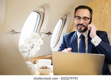 Portrait of glad diplomat in airplane talking by cellphone and looking at notebook screen. Copy space in left side