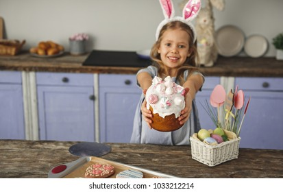 Portrait of glad female child in kitchen holding tasty easter cake with beautiful glaze on top. Focus on dessert. Copy space in left side