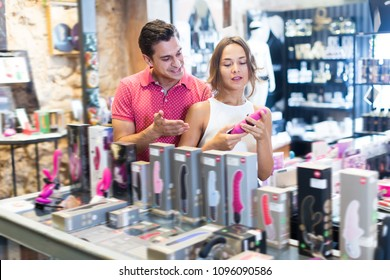 Portrait of glad girl and man consumers holding sexy toys in the sex shop