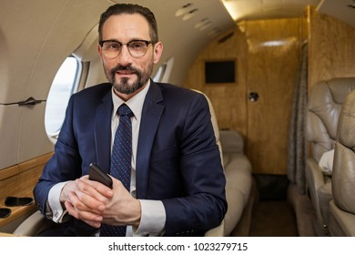 Portrait of glad groomed mature male in suit relaxing in airplane seat. Copy space in right side