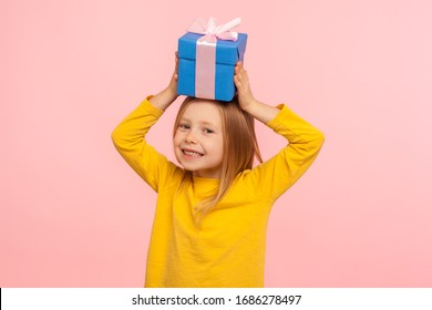 Portrait of glad happy little girl holding gift box on head, having fun with present and smiling joyfully to camera, birthday or Christmas celebration. indoor studio shot isolated on pink background