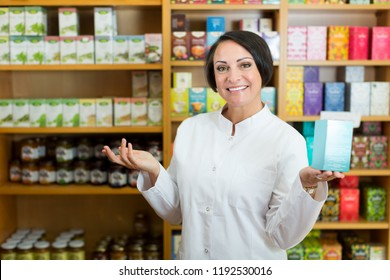 Portrait of glad mature female pharmacist with biologically active dietary supplement package
