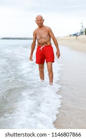 Portrait of glad mature man checks the water temperature on the beach