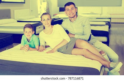 Portrait glad parents with young son testing mattress in store