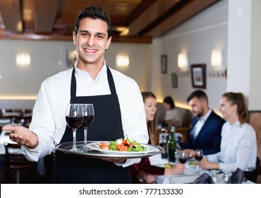 Portrait of glad  smiling waiter with serving tray meeting restaurant guests