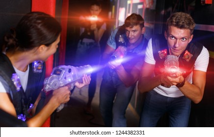 Portrait of  glad smiling young friends playing laser tag  game  with laser guns in dark corridor
