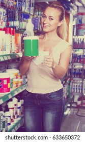 portrait of glad woman customer taking paint can in housewares department