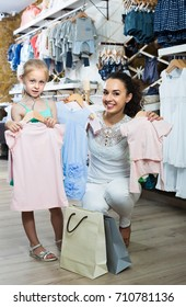 portrait of  glad woman and girl shopping kids apparel in clothes store