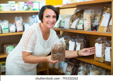 Portrait of glad woman with groats in hands in pharmaceutical store