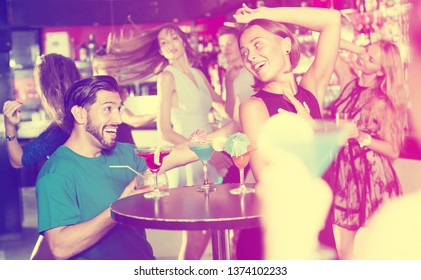 Portrait of glad woman with man are having fun in the nightclub.