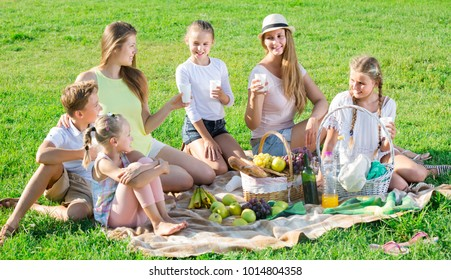 Portrait of glad women with happy children on picnic in summer park