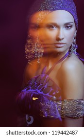 portrait glamor girl in violet evening dress and beautiful jewelry in motion lights blur