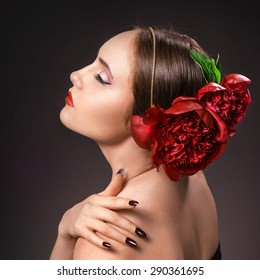 Portrait of glamorous brunette girl over dark background with burgundy peony in hairs. Evening make-up, red lips, strong black arrows.