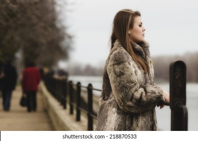 Portrait of the glamorous brunette lady in expensive fur coat watching river.