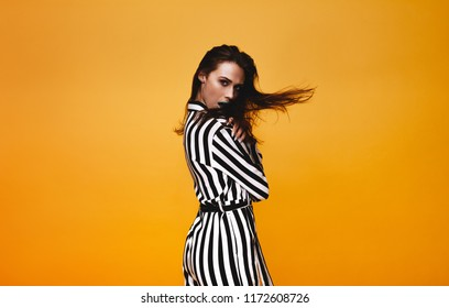 Portrait of glamorous female model in studio. Attractive woman in striped jumpsuit looking at camera with hair flying against orange background.