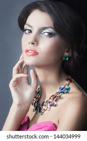 portrait of a glamorous girl with black hair and an expensive necklace with precious and colored stones