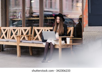 Portrait of glamorous hipster girl sitting with portable laptop computer on a cozy bench near coffee shop, young funky woman with nice look connects to the Internet via net-book though cafe wireless