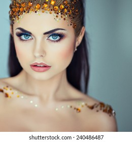 Portrait of a glamorous very beautiful girl brunette with sequins on the face, close up