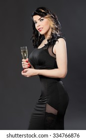 Portrait of glamorous young woman in black dress holding a glass of champagne