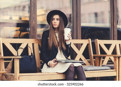Portrait of a glamorous young woman holding on her knees portable laptop computer while sitting on a wooden bench, stylish female drinking coffee while relaxing after work on net-book during free time