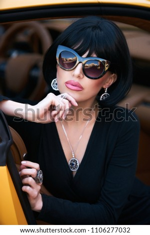 Portrait of Glamour brunette babe sitting in yellow supercar. Young woman  with black hair and red lipstick posing in sport car - Image d667d2143