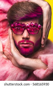 Portrait of glamour man with red beard. Guy in a pink fur coat and funny  sunglasses.