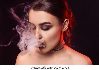 Portrait of glamour seductive gorgeous brunette woman smoking electronic cigarette in studio