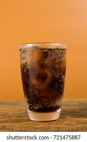 Portrait of a glass with cola soda drink with ice cube on rustic wooden table in orange background
