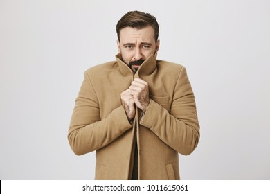 Portrait of gloomy bearded man who is freezing, holding tight his coat to warm up, standing over gray background. Sometimes weather act unpredictably. Guy regrets not to wear warmer clothes