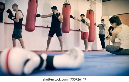 Portrait of gloves and  boxers  beating boxing bag on background