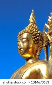Portrait A golden Buddha statue on blue sky background