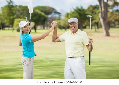 Portrait of golfer couple giving high five while standing on field