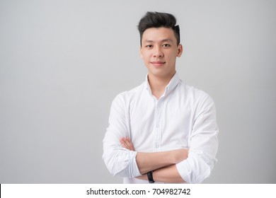 Portrait of good looking asian man over gray background.