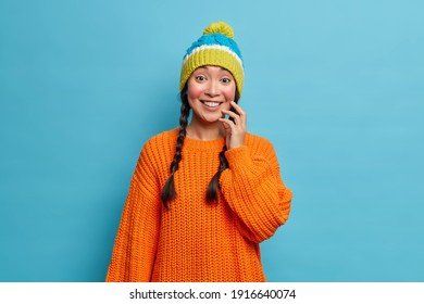 Portrait of good looking Asian millennial girl with two pigtails touches face gently has rouge cheeks from frost smiles broadly wears knitted winter hat orange sweater isolated over blue background.