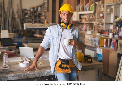 Portrait of a good looking cheerful carpenter holding a coffee mug and taking a break from work.
