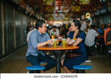 Portrait of a good looking Chinese Asian couple enjoying a snack at a hawker center during the weekend in Singapore, Asia. They are smiling as they talk and enjoy sugarcane juice and fried bananas.