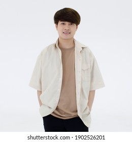 Portrait of a good looking and confident young Asian man with stylish hairdressing wearing a casual white shirt over a light brown T-shirt smile and looking at a camera isolated over white background.