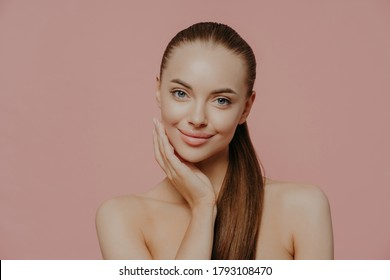 Portrait of good looking female has long straight hair combed in pony tail, stands shirtless, has clean perfect skin, satisfied with her natural beauty, poses indoor against pink background.