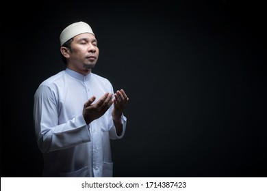 Portrait A good looking middle-aged Asian muslim man is praying for prayer with faith and determination. on black background, with copy space.