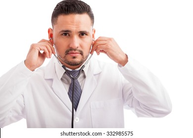 Portrait of a good looking young Latin doctor putting his stethoscope on before examining a patient